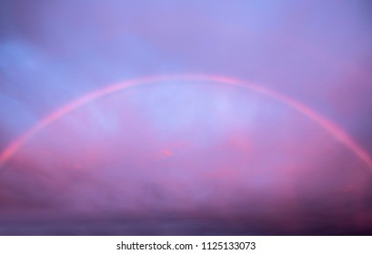 Entire rainbow arc at nightfall against purple pink sky at sunset. The most spectacular rainbow displays happen when half the sky is dark with raining clouds at sun down. Not manipulation.