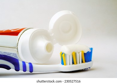 Entire tube of toothpaste with a toothbrush close-up on white background