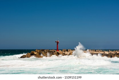 Entrace to the Durban port during sunny day lighthouse on the rocks and splashing waves and fisherman
