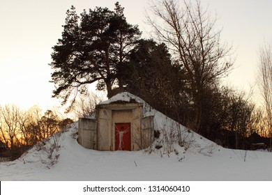 Entrance to abandoned fallout shelter building - door and concrete wall on snowy winter day