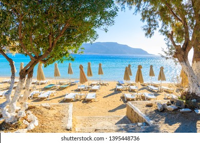 Entrance to Ammopi beach with umbrellas and chairs on Karpathos island, Greece