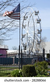 Entrance to an amusement park, with American flag and ferris wheel. All American Summer of Fun.