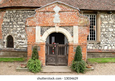 Entrance arch and gates to a Medieval Brick and Flint English Village Church