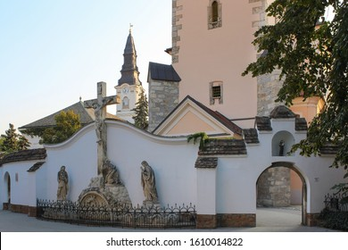 Entrance to the backyard of St Nicholas Franciscan church with a sculpture composition at fence wall - Kecskemét purgatory relief, made 1792, remnant of Calvary of the Cemetery, in Kecskemét, Hungary