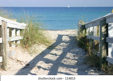 Entrance to the beach with sailboat on the ocean