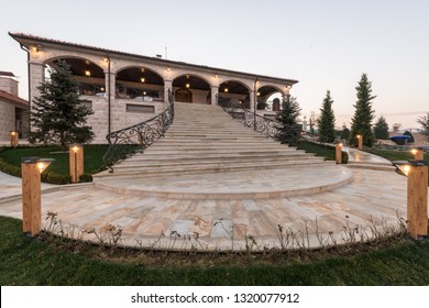 Entrance with big marble stairs of mansion by dusk