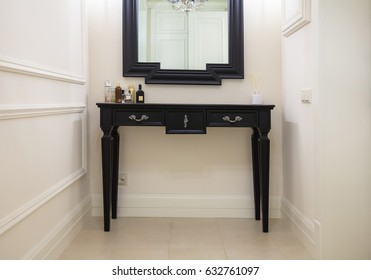 Entrance with black wooden console, a mirror and decor