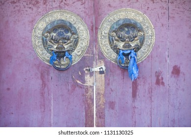 Entrance to a Buddhist temple, with scarves and lion heads.