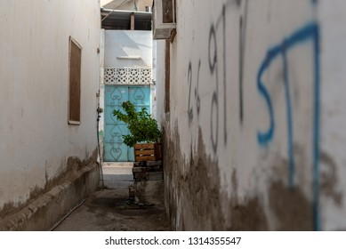 Entrance building blue door, narrow lane and graphitis in the historical district of Matrah, City of Muscat, Sultanate of Oman.