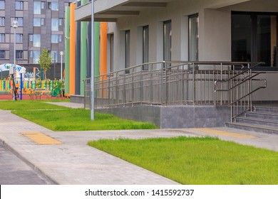 Entrance to building. Staircase with metal railing. Entrance group in small ofice and colorful facade. Stair steps up and down. Kindergarten, school or hospital. Main entrance