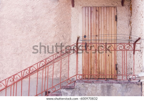 Entrance to the building through a brown wooden door. Steps with metal handrail