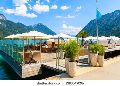 Entrance to cafe on pier on shore of beautiful Achensee lake on sunny summer day, Tirol, Austria
