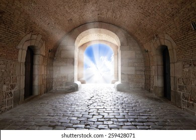 The entrance of the Castillo de Montjuïc, with sunlight shining at the end of the tunnel, blue sky and white clouds, like a path to the gate of heaven