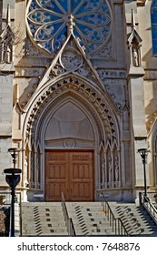 Entrance to the Cathedral of St. Helena in Helena, Montana.  Notice huge wooden doors, cherub faces, Gothic architecture, statues, and more.