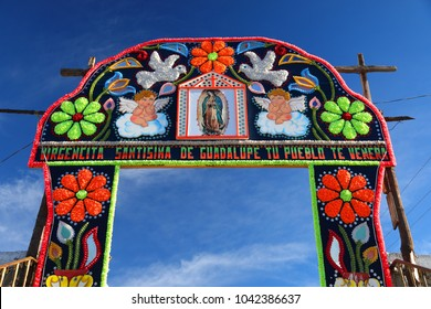 "entrance to a church in a Mexican village with a sign of flowers craft and the Guadalupe Virgen image ,that says, ""virgen of Guadalupe blessed, your people adore you"""