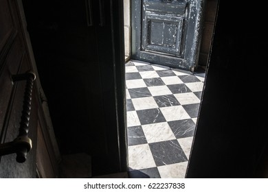 Entrance of a church. The old wooden door is open and light is shining on a stone checkered floor
