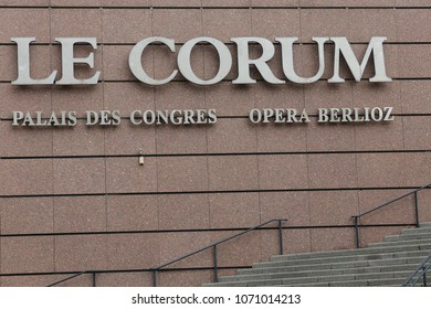Entrance of the congress building and opera called le corum, in montpellier city, France. April, 15, 2018. View of the principal pink facade with name inscription. Large staircase with iron handlebars
