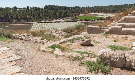 the entrance courtyard and official rooms at the tel lachish archaeological site in Israel with moshav lachish in the background