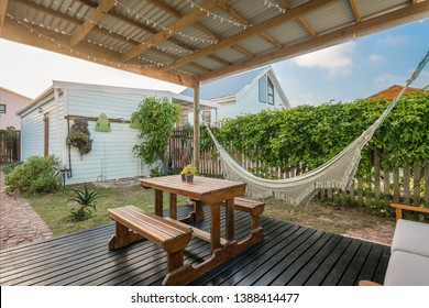 Entrance of a cozy residential property, comfortable porch for entertaining, with wooden deck floor, picnic table, hammock, bench with cushions and a green garden around