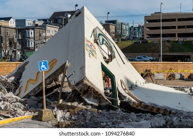 The entrance to a demolished parking garage. Handicapped sign and part of universal parking P symbol visible. Rubble on ground.
