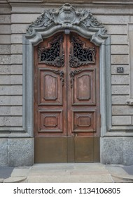 entrance door of an ancient building with elegant wrought iron decorations at number 24 of a street in Milan, Italy