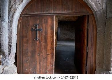 The entrance door to the ancient temple with a cross on the door and handles forged by a blacksmith.