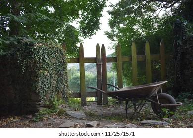 Entrance door to an orchard and an old wheelbarrow