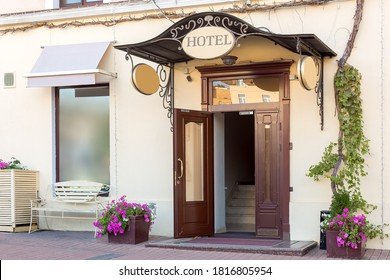 entrance door with a threshold and a visor with a hotel sign on the facade of the building with a flowerpot, european cityscaep nobody.