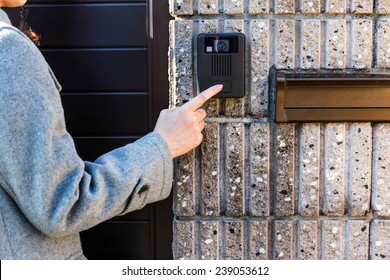 At the entrance door, woman ringing at the door bell