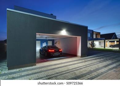 Toegang tot een garage met de stralende lampen in het moderne landhuis. In de garage is er een zwarte auto met gloeiende parkeerlichten. Rondom het huis is er een betegelde ruimte. Horizontaal.