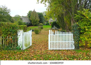 Entrance to the garden of a country house with white wooden gates in autumn. French style.