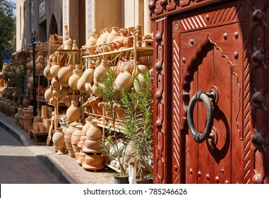 Entrance of the gate door of the town of Nizwa in Oman. Also a view on a pottery shop.