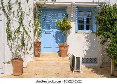 Entrance gate to typical Greek style apartments decorated with flower pots on street in Chora town on Folegandros Island. Cyclades, Greece