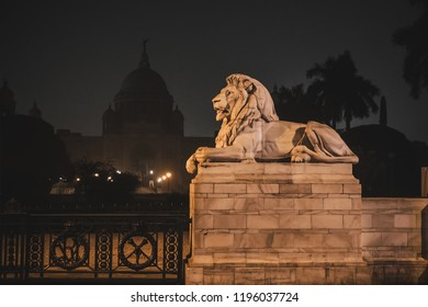Entrance gate with white marble lions of Victoria Memorial architectural monument and museum at Kolkata, India. White lion sculpture in the night light.