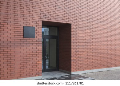 Entrance with a glass door to the modern office center. Loft style, red brick and laconic black sign at the entrance