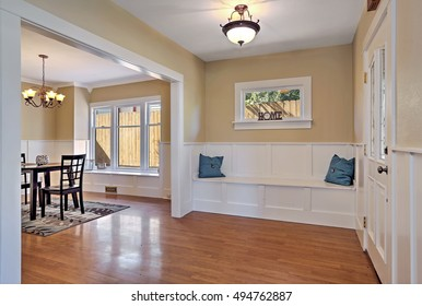 Entrance hall with wood paneled walls and comfortable seat with pillows. Dining room in the background