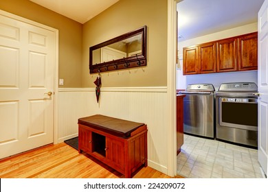 Entrance hallway with mirror and storage cabinet. Laundry room with steel appliances