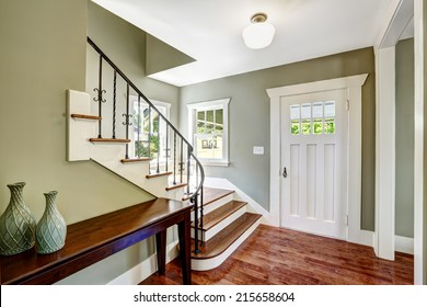 Entrance hallway with staircase and table. View of steps with wrought iron railings