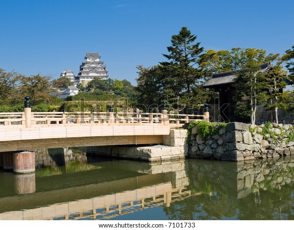 Entrance to Himeji Castle grounds surrounded by a moat with main gate and bridge crossing in the foreground and Himeji Castle with clear blue sky in the background