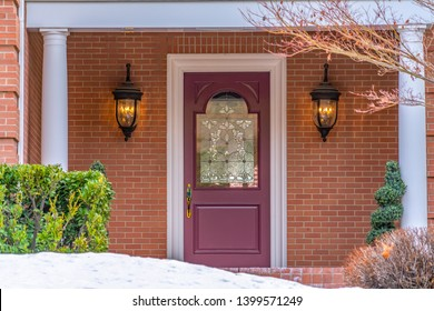 Entrance of a home with a beautiful front door and snowy yard in winter