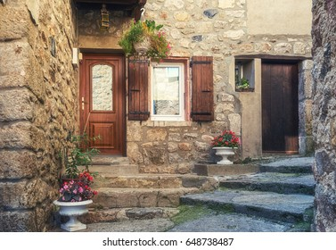 The entrance  of a house in a narrow street of the picturesque village of Antraigues-sur-Volane in the Ardèche department in the Auvergne-Rhône-Alpes region of southern France.