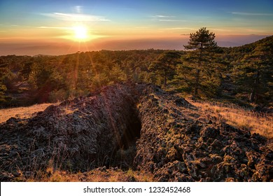 entrance of lava tube formed by volcanic activity in Etna Park at the sunset in Sicily