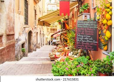 Eintritt in den örtlichen Laden in Taormina, Sizilien. Das Schreiben auf der schwarzen Tabelle listet die Zeitpunkte der Werbung auf.