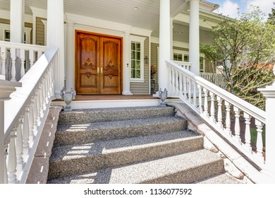 Entrance to a luxury country home with wooden front door, covered deck, white columns and staircase.