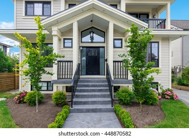 Entrance of a luxury house with beautiful landscaping on a bright, sunny day.