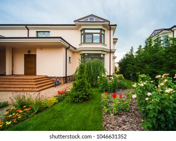 Entrance of a luxury house with a patio and beautiful landscaping on a bright, sunny day. Home exterior.