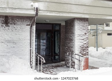 Entrance of modern high-rise apartment building covered with snow and frost after heavy windy snowstorm Snowfall and blizzard aftermath in winter. Cold snowy weather forecast