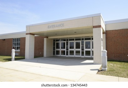 entrance for a modern school, with a covered entryway and sidewalk