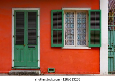 Entrance of New Orleans, Louisiana USA home, red with green door and shutters in French Quarter