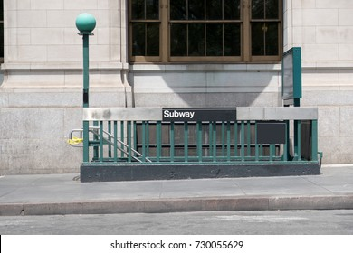 Entrance to the New York City subway. Stairs leading down to a subway station in Manhattan. iconic green lamps that mark the entrance to a subway station. No people.